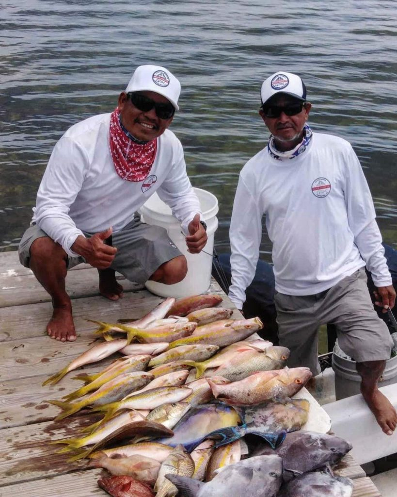 Belize Guide Co. captains in their white hats and shirts displaying the fish caught on the pier while on tour.